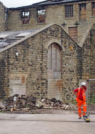 hebden bridge, west yorkshire, united kingdom - 2 august 2019: man working at the demolition of walkeys mill building in hebden bridge after the fire on 1st of august 2019 Redactioneel