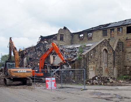 hebden bridge, west yorkshire, united kingdom - 2 august 2019: construction machinery at the demolition of walkeys mill building in hebden bridge after the fire on 1st of august 2019