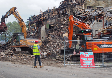 hebden bridge, west yorkshire, united kingdom - 2 august 2019: a man on crutches in protective work clothes construction machinery at the demolition of walkeys mill building in hebden bridge after the fire on 1st of august 2019 Redactioneel