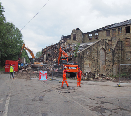 hebden bridge, west yorkshire, united kingdom - 2 august 2019: men and construction machinery at the demolition of walkeys mill building in hebden bridge after the fire on 1st of august 2019