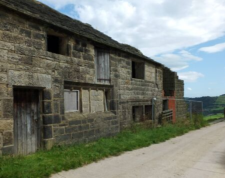 ancient abandoned stone cottage in a row of rural buildings with empty windows and wooden doors with the pavement overgrown with grass Imagens