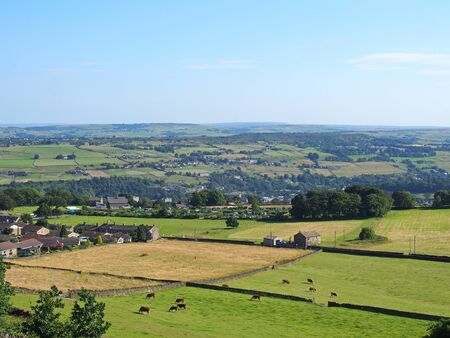 an aerial panoramic view of west yorkshire countryside near luddenden with cows grazing in meadows and farmhouses with the village and woodland in the distance