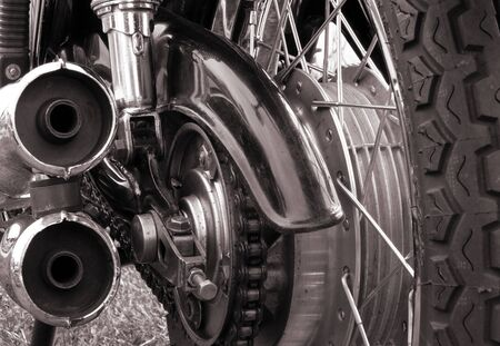 close up rear view of a vintage motorcycle with tyre treads wheel spokes drive chain and shiny chrome springs Stock Photo