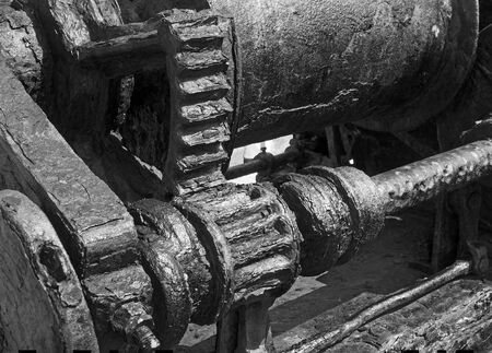 monochrome image of rusted cogs and gears on an old broken industrial machine