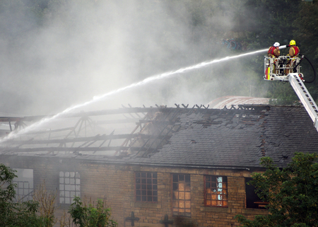 hebden bridge, west yorkshire, united kingdom - 1 august 2019: firemen on an elevated platform putting out the fire at the former walkeys clogs mill in hebden bridge Redactioneel