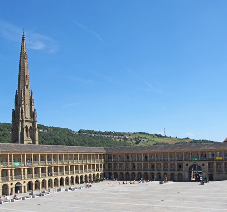 halifax, west yorkshire, united kingdom - 23 july 2019: people relaxing and enjoying the summer sunshine in the square of halifax piece hall in west yorkshire with surrounding hills and old church