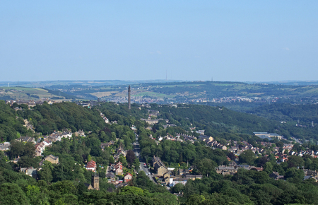 a panoramic view of the town of west yorkshire from above with streets and houses surrounded by trees and fields and the historic wainhouse tower on a hillside Redactioneel