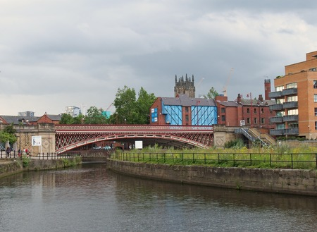 leeds, west yorkshire, united kingdom - 10 july 2019: riverside view of crown point bridge crossing the canal and aire in leeds with people on the waterside pathway and surrounding city buildings