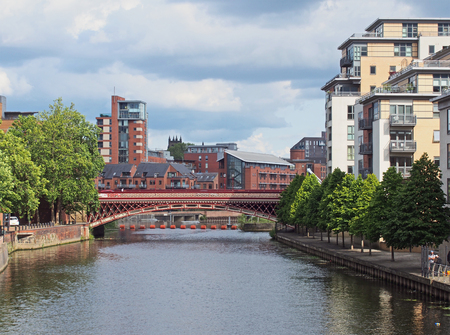 leeds, west yorkshire, united kingdom - 12 july 2019: a view along the river aire in leeds with waterside apartments and buildings with crown point bridge crossing the water Redakční