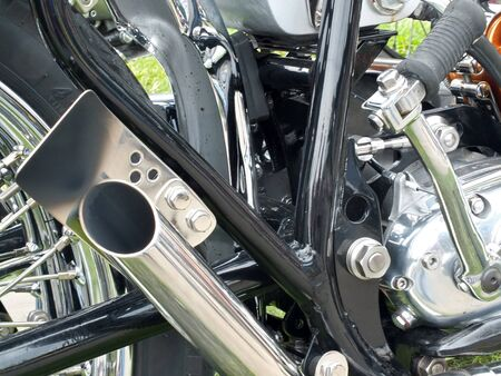 close up of the engine and chrome exhaust pipe of a vintages custom 1970s scrambler type motorcycle Reklamní fotografie