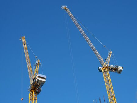 two tall yellow tower cranes working on a construction site against a blue sky Stockfoto