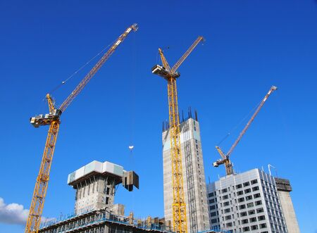 cityscape view of tall tower cranes working on large construction sites against a blue sky in leeds england
