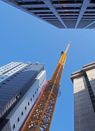 vertical view of a tall yellow construction crane working on a new concrete building with large surrounding towers