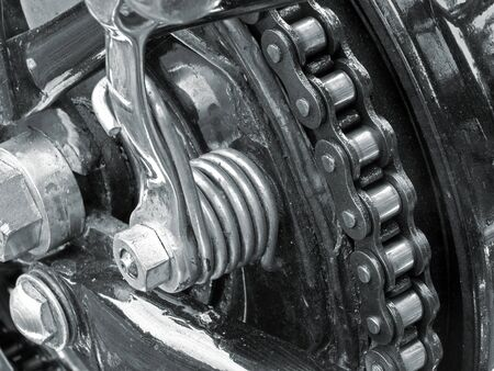 monochrome close up of the drive chain on a black vintage motorbike with chrome fixtures and steel bolts Reklamní fotografie