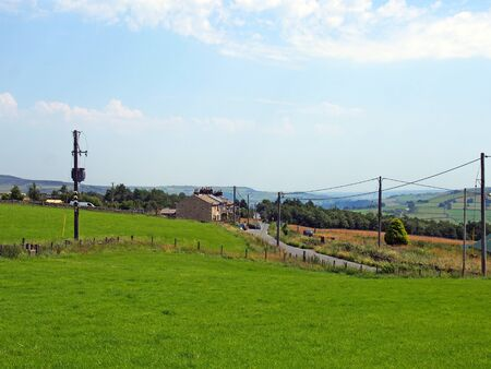 houses in the village of blackshaw head in west yorkshire with a road running thought fields with distant farmhouses and pennine hills against a blue summer sky