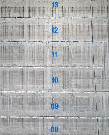 the surface of a concrete service tower core of a building under construction with the floor numbers marked in blue paint Reklamní fotografie