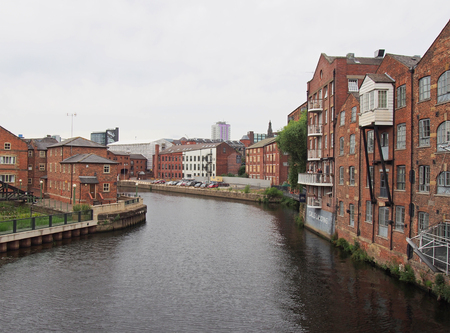 leeds, west yorkshire, united kingdom - 4 july 2019: riverside view of the calls landing area of leeds with waterfront apartments and buildings reflected in the river aire