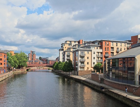 leeds, west yorkshire, united kingdom - 16 july 2019: a view of the river aire in leeds with apartment buildings around crown point bridge and people walking along the waterfront Redakční