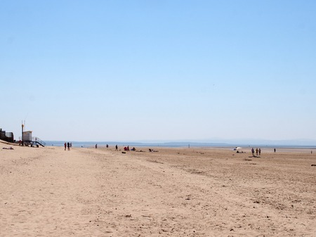 sefton, merseyside, united kingdom - 27 june 2019: people walking and relaxing on formby beach on the sefton coast in merseyside with blue summer sea and sky