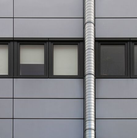 grey cladding panels on an industrial building with a row of back window frames and a silver pipe running up the wall Reklamní fotografie