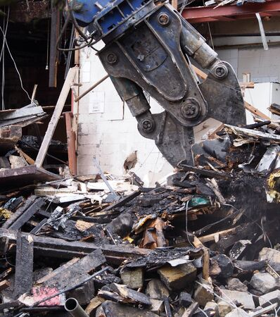 close up of a demolition claw working picking up debris in the wreckage of a destroyed building