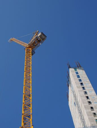 a yellow tower crane working on a construction site with a tall concrete building against a bright blue sky