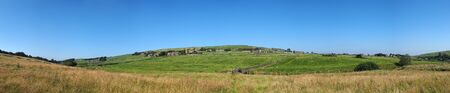long panoramic view of green fields and village houses and ancient packhorse bridge in rolling west yorkshire dales countryside in colden with blue summer sky