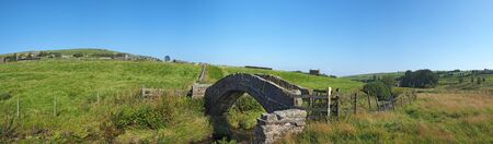 a panoramic view of an ancient stone packhorse bridge crossing a stream in west Yorkshire dales countryside with the village of colden in the background