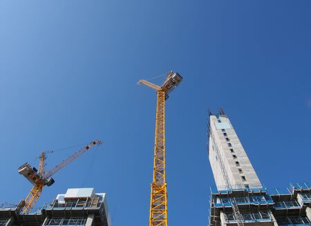 a view of tall tower cranes working on large construction sites against a blue sky in leeds england