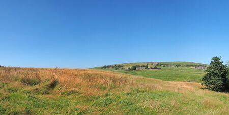 long panoramic view of green fields and distant village stone houses in rolling west yorkshire dales countryside in colden with blue summer sky Reklamní fotografie