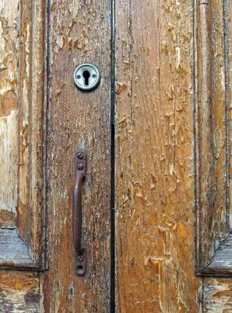 close up of an old brown varnished peeling wooden door with keyhole and rusty handle
