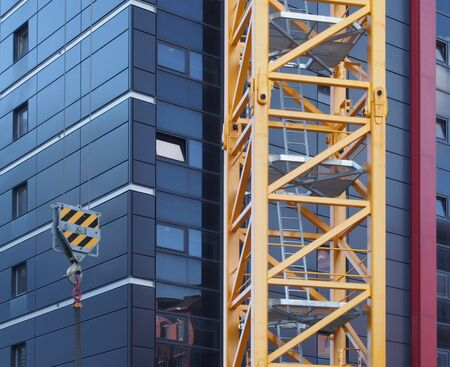 close up of the tower of a yellow construction crane with steel ladders lifting a hook with chain against a modern black building under construction
