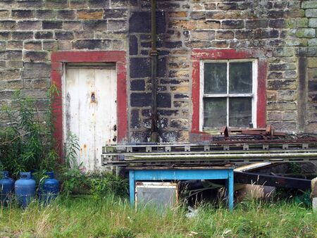 the facade of a shabby abandoned rural house with dirty windows and peeling paint overgrown with weeds with scrap and junk piled outside