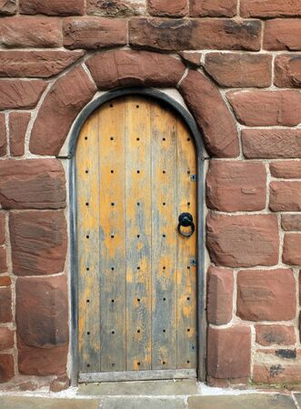 an ancient brown wooden door in a red sandstone medieval wall Фото со стока