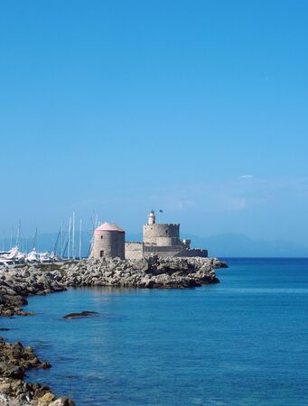 boats moored near the tower and fort of saint nicholas on the old harbour in rhodes town