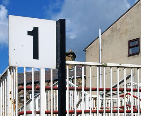 a railway station platform sign with the number 1 next to shabby painted railings on a small local train station in northern england