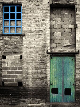 vintage style colorized image of an abandoned industrial warehouse and factory building with blue windows and green door