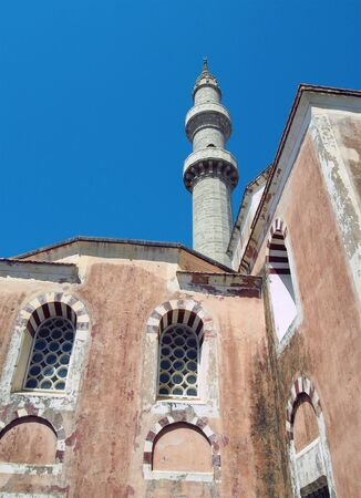 the suleiman mosque in rhodes old town with tall minaret against a blue sunlit sky Фото со стока