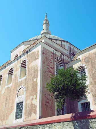 the suleiman mosque in rhodes old town with dome and tall minaret against a blue sunlit sky