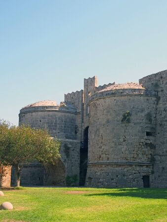 the amboise gate in the medieval walls of the old city in rhodes town surrounded by grass and trees Фото со стока