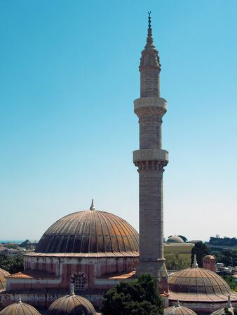 the domes and minaret of the suleiman mosque in rhodes old town with tall minaret against a blue sunlit sky