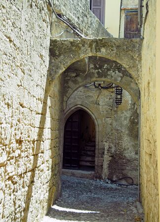 a narrow alleyway in rhodes old town with arches between old stone walls and an open doorway with stairs inside