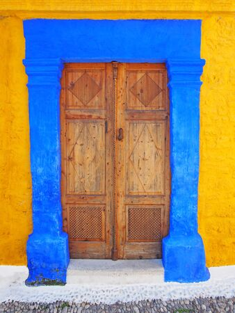 old ottoman style ornate wooden door double in a bright blue painted stone frame set in a yellow wall in rhodes town greece