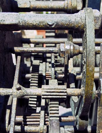 a close up of complex gears and cogwheels on old rusting steel machinery