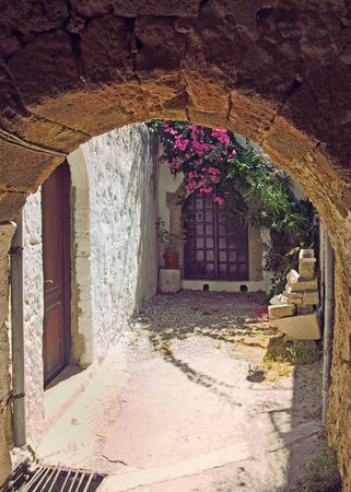an ancient sunlit alleyway in rhodes town under a stone arch with flowers growing over a doorway