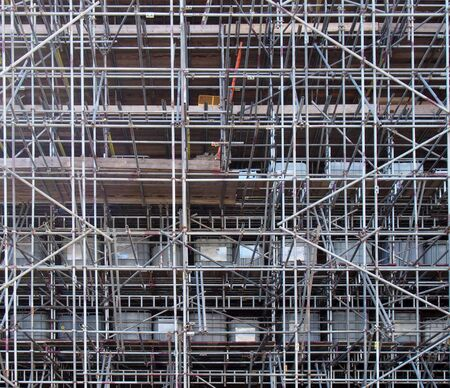 a full frame image of a network of scaffolding covering a large building under renovation 스톡 콘텐츠