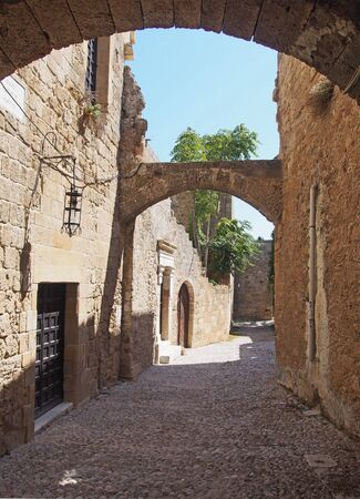a quiet medieval cobbled street in rhodes town with old buildings and arches between stone buildings