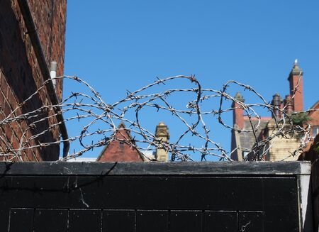 barbed wire on top of a wooden fence surrounded by urban buildings against a blue sky Фото со стока