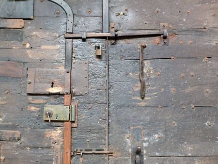 ancient black wooden medieval door with iron locks and bolts on chester cathedral Фото со стока