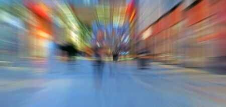 abstract zoom blur of a modern city street at night with people walking and bright illuminated buildings Фото со стока